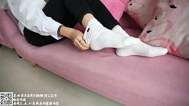 Chinese girl takes off white crew sock to reveal low cut ankle sock inside