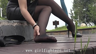 Chinese beauty massages her sprained foot in black pantyhose