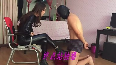 Chinese mistress in a bodysuit dominates her slave with Doc Martens