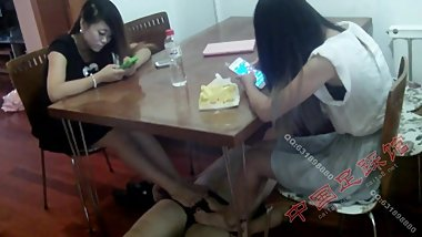 two girls giving a footjob under table while playing phones