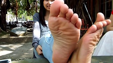 Shy asian student shows her soles